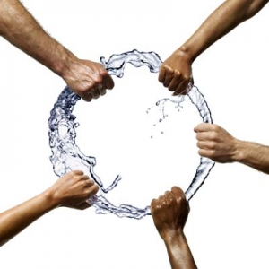 Group of hands hold a circle of water